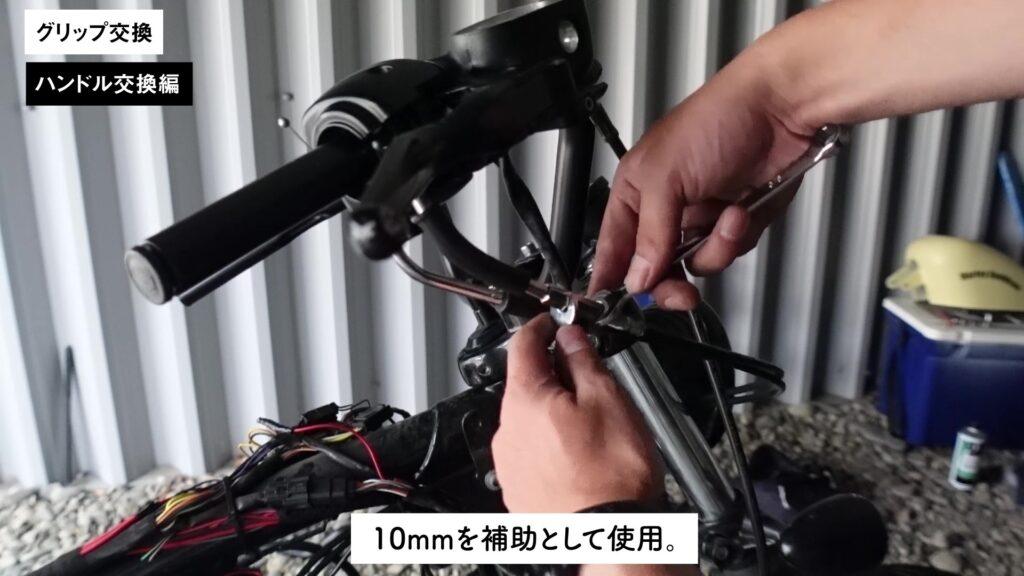 アクセルワイヤーを緩めるために3/8インチのレンチを使う